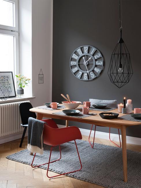 Fragment jadalni z biało-antracytową ścianą, drewnianym stołem oraz czerwonym fotelem