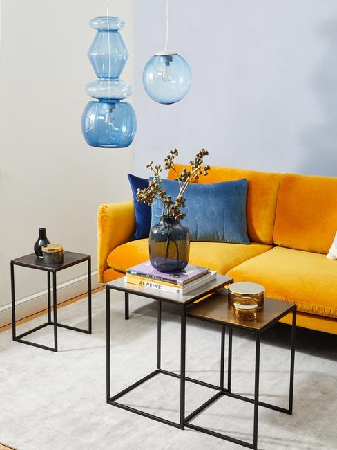Sofa w kolorze ochty z białym salonie z niebieskimi dodatkami w postaci lampy oraz poduszek
