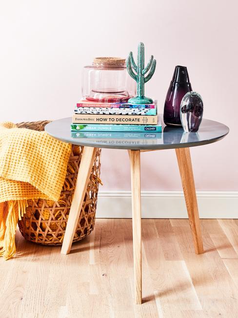 Zbliżenie na drewniany stolik ze szklanym blatem oraz kosz w kolorze ochry