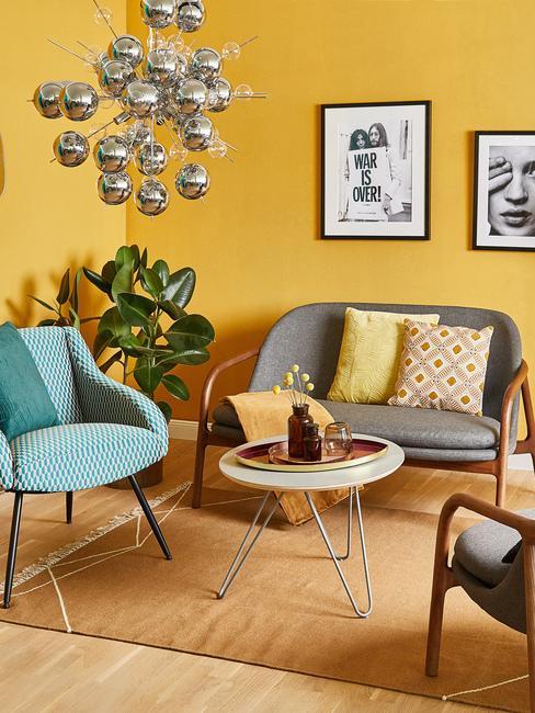 Salon o ścianach w kolorze ochry, szarą sofą, turkusowym krzesłem oraz srebrnym żyrandolem