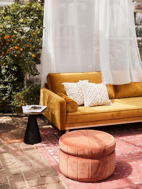 Sofa w kolorze ochry ustawiona na tarasie