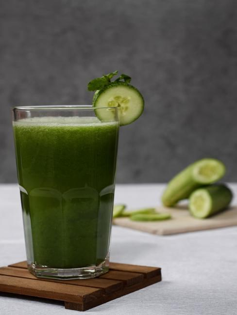 Zielone smoothie w wysokiej szklance na drewnianym podstawce