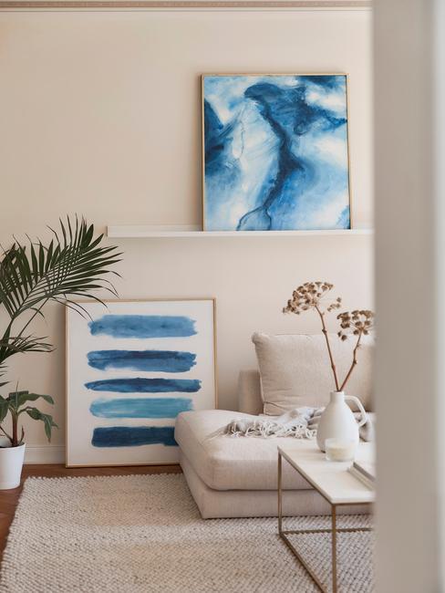 Fragment beżowego salonu z niebieskimi obrazami, sofą, białym stolikiem kawowym oraz palmą w doniczce