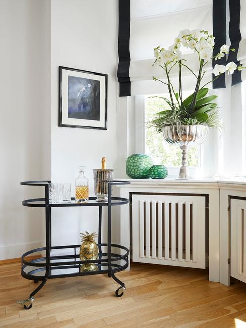 Duży kwiat storczyka na parapcie w pomieszczeniu z czarnym wózkiem barowym