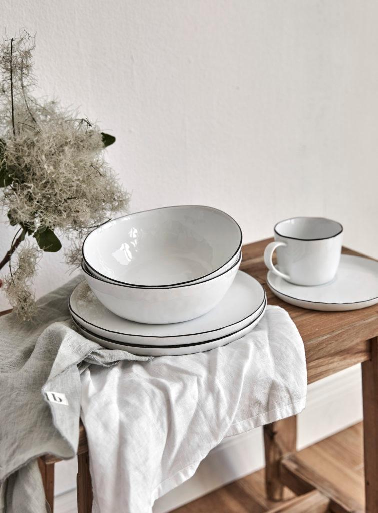 Zestaw talerzy, misek oraz filiżanki ze spodkiem ystawiony na drewnianym stole