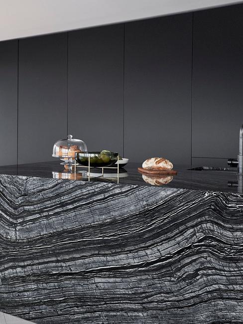 Czarna kuchnia z szafkami oraz blatem kuchennym wykonanym z czarnego marmuru