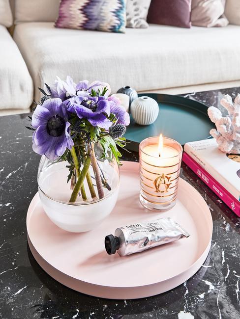 Stolik kawowy z czarnego marmuru. Na nim taca z wazonem i świecą