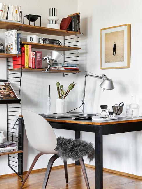 Fragment sypialni z drewnianym biurkiem, lampką oraz drewnianymi półkami