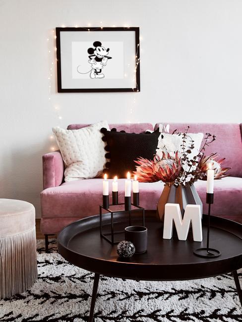 Salon z różową sofą i czranym stolkiem, na którym stoi ozdobna litera