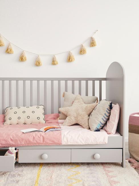 Szarne łóżeczko dla dzieckanad którym wiszą dekoracje