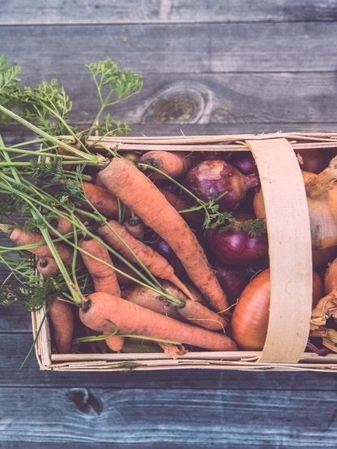Warzywa w wiklinowym koszyku położone na stole