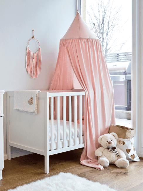 Łóżeczko z baldachimem w pokoju dla dziewczniki, łapaczen snów oraz pluszowym misiem