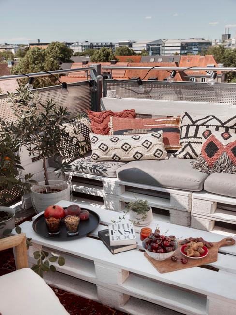Balkon w mieście z sofa oraz stolikiem kawowym zrobionyi z europalet oraz dekoracje