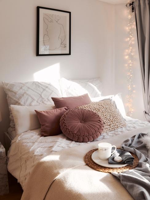 Łóżko z poduszkami dekoracyjnymi oraz girlanda świetlną
