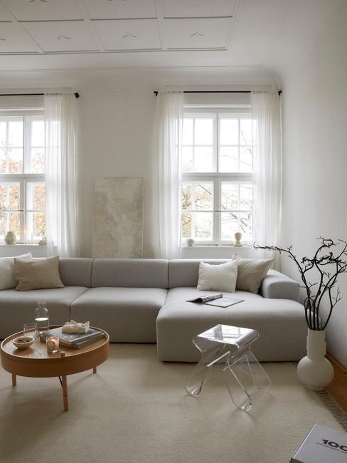 Salon z szarą sofa, drewnianym stoliczkiem z dekoracjami i wazonie z gałązką