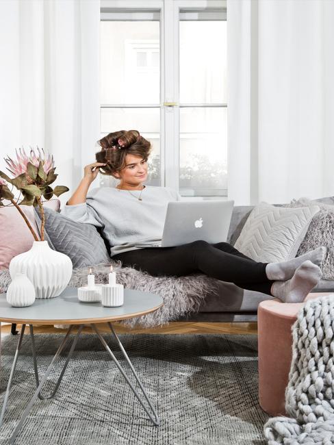 Kobieta siedząca na sofie z wielona poduszkami przy okrągłym stoiku w domowym biurze