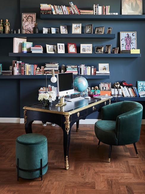 Biuro homowe w stylu glam z niebieską ściną, obszernym regałem oraz aksamitnym fotelem