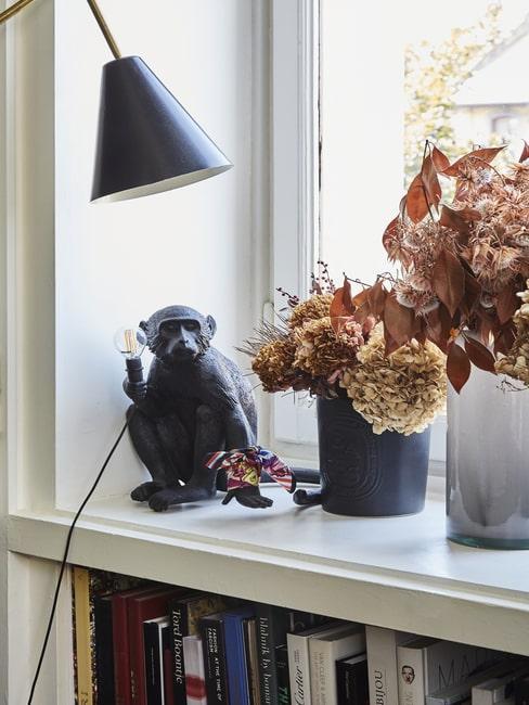 Parapet z szułonymi kwiatami w wazonie i lampka małpka
