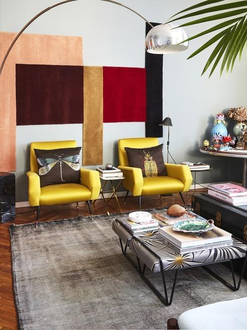 Salon z zółtymi fotelami i ścianą w różnych kolorach