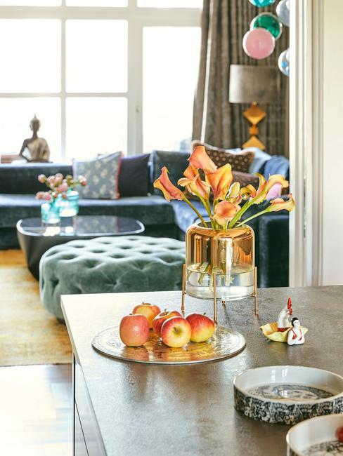 Fragment salonu połączonego z jadalnia, w którym znajduje się niebieska sofa oraz stolik kawowy