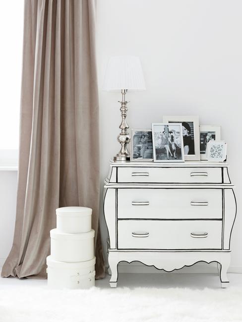Biała, elegancka komoda stojąca obok beżowej zasłony w salonie