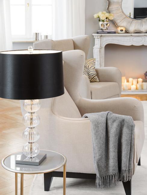 Fragment salonu w stylu nowojorskim z beżowym fotelem i czarną lampą