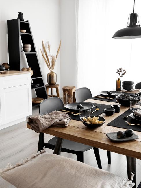 Jadalnia z drewnianym stołem i czarnymi krzesłami oraz czarnym regałem i dekoracją z trawy pampasowej