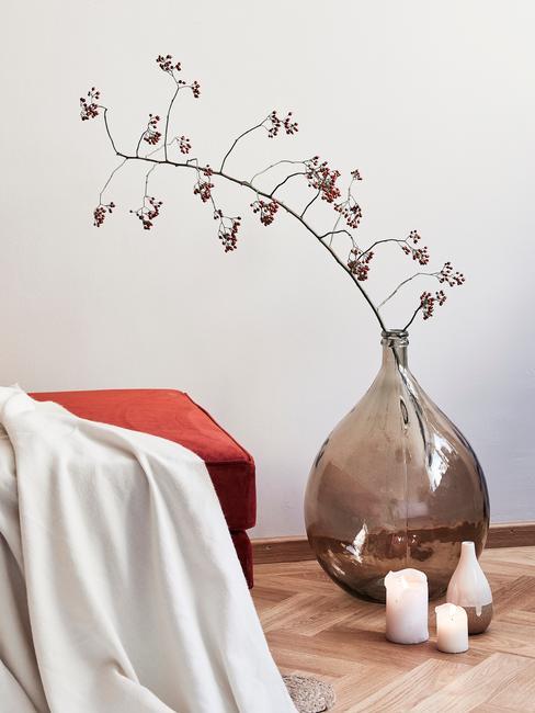 Wazon ustawiony na podłodze z kwiatem stoający obok pomarańczowego pufu
