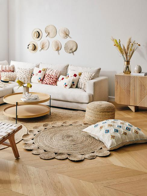 Salon w stylu boho z białą kanapą, okrągłym stolikiem, dywanem oraz dekoracjami