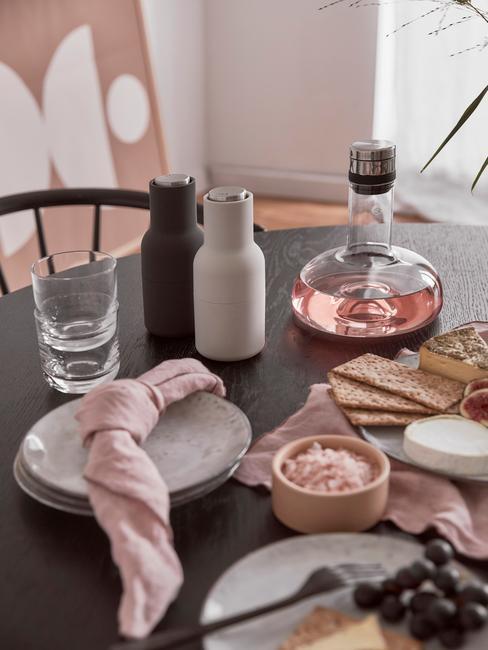 Zastawiony stół z talerzami, solniczką i peiprzniczką oraz serwetkami w kolorze brudnego różu