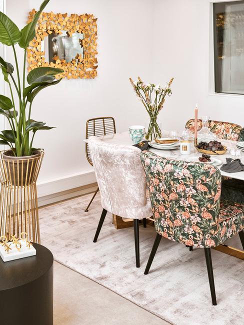 Fragment jadalni z różymi krzesłami oraz zastawionym stołem