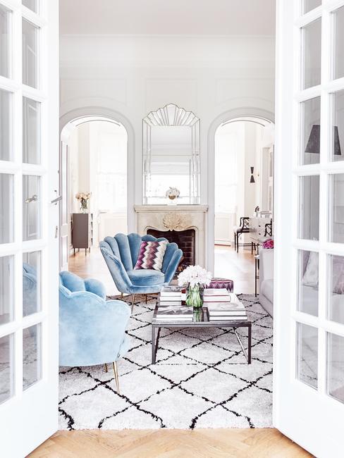 Salon w stylu nowojorskim z turkusowymi fotelami, fanapą, stolikiem kawowym oraz kominkiem