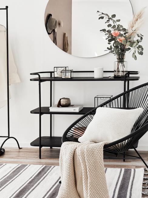 Fragment salonu z czarnym, plecionym fotelem, czarnym stolikiem i okrągłym lustrem