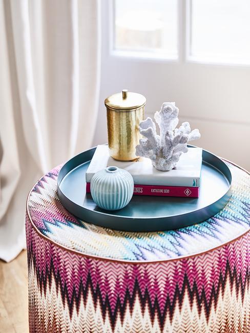 Różnobarwny puf w salonie, na którym ułożona jest niebieska taca z dodatkami
