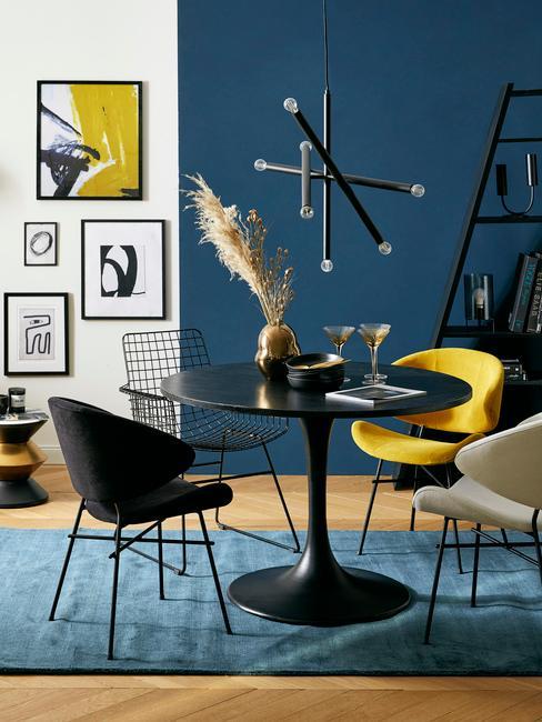 Salon z granatową ścianą, czarnym stołem i żółtymi dodatkami