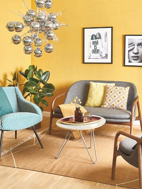 Salon pomalowany na żółto z szarą sofą, niebieskim krzesłem oraz stolikiem kawowym