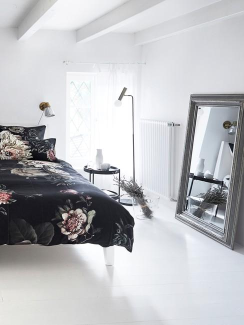 Fragment sypialni z łożkiem, stolikiem nocnym, lampą oraz suszoną lawendą w wazonie
