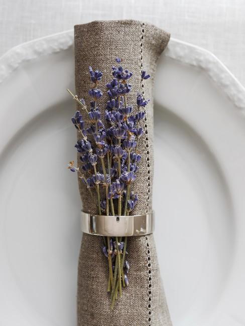 Lniana serwetka z suszonymi kwiatami lawendy z złotym pierścieniu ułożona na białym talerzu