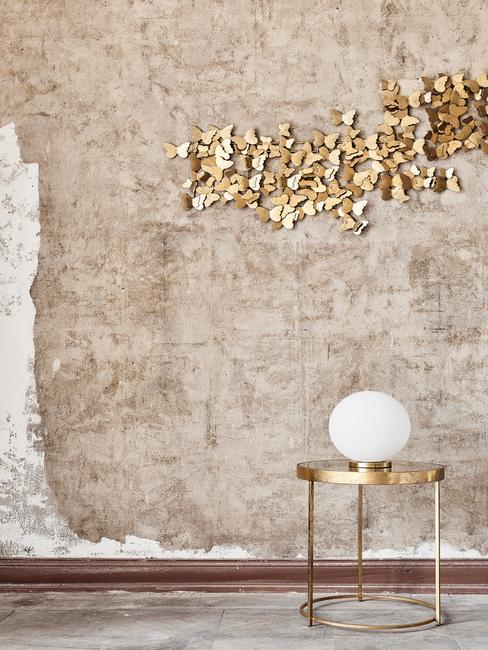 Betonowa ściana w pomieszczeniu na której wiszą złote dekoracje w motyle oraz złoty stolik z lampą