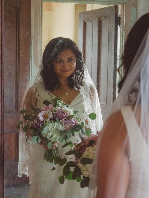 Panna Młoda stojąca przed lustrem z bukietem kwiatów