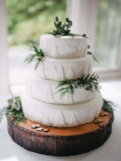 Tort weselny ozdobiony roślinami postawiony na tacy zrobionej z pienia drzewa