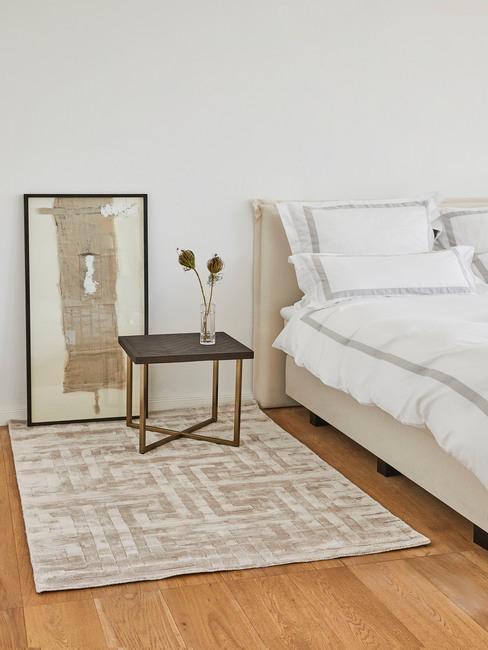 Biała sypialnia z łóżkiem, czarnym stolikiem nocnym, obrazem oraz kremowo-szarym dywanem