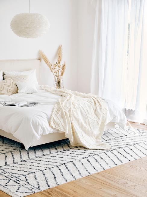 Biała sypialnia w stylu boho z łożkiem, kremowym kocem, kwiatami oraz czarno białym dywanem