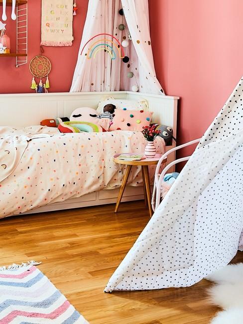 Różowy pokój dzewczynki z białym łożkiem, namiotem tipi oraz zabawkami