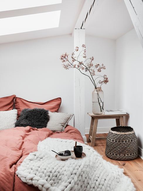 Biała sypialnia na poddaszu z łóżkiem o różowej pościeli stolikiem nocnym oraz koszem plecionym