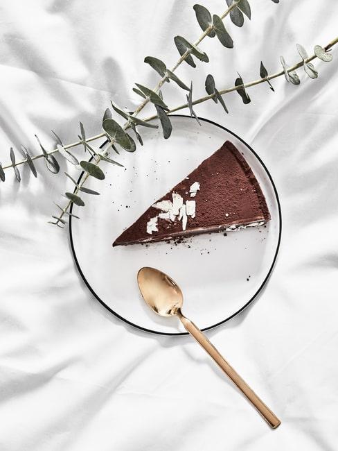 Kawałek ciasta na białym talerzyku w łóżku