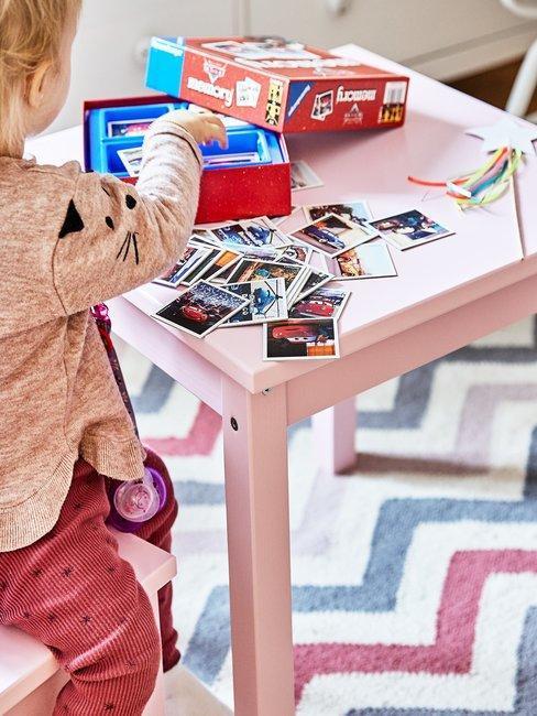 Dziecko siedzące przy różowym stoliku na tkórym są rozłożone karty oraz inne gry
