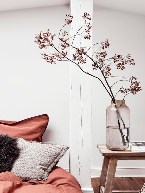 Biała sypialnia z drewnianym stolikiem z wazonem z kwiatem oraz łóżkiem z pomarańczową pościelom