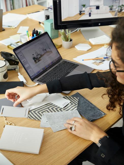 Kobieta siedząca przy drewnianym diurku, na którym znajduje się laptop, monitor oraz próbki kolorów