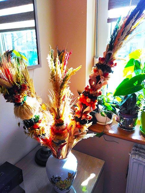 kolorowe palmy wielkanocne w białym wazonie na komodzie